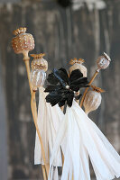 Poppy seed heads painted with patterns and paper flower