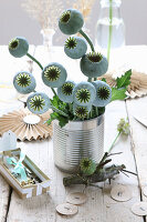 Bouquet of fresh poppy seed heads in tin can and paper decorations