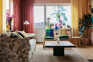 An upholstered sofa with a floral pattern, a coffee table and colourful curtains in a living room