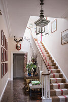 Mounted Ibex head in front hall, jute runner on the staircase