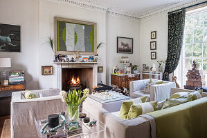 Elegant drawing room with chairs and sofa from, linen covers and a zebra photography to the right of the fireplace