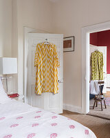 Calm guest bedroom in fuchsia and white , a brightly coloured pasha hangs from the back of the door and there is an open doorway to the ensuite bathroom
