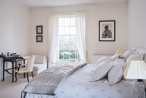 Silk eiderdown on bed in tranquil bedroom with writing desk and French chair upholstered in silk