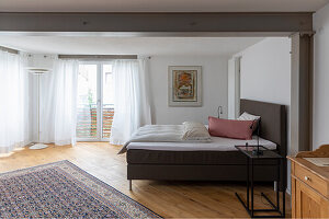 Double bed in bedroom with pale floorboards