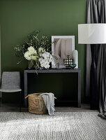 Konsole mit üppigem Blumenstrauß vor grüner Wand
