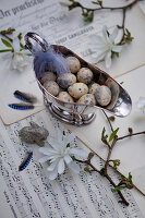 Silberne Sauciere mit Ostereiern und Feder, Zweige der Sternmagnolie, Osterhase und Federn vom Eichelhäher