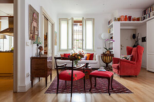 Red chairs, antique chest of drawers, chests as coffee table, sofa and armchair in living room