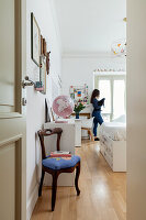 Room with antique chair and white modern furniture, girl with cat in the background