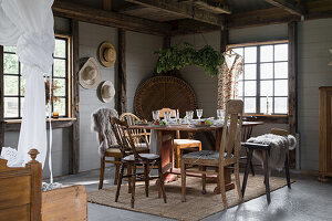 Set dining table with various chairs in renovated forge