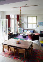 Wooden dining table with chairs, above it colourful pendant lamp in open living area