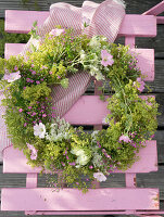 Wreath of lady's mantle, mallows, Queen Anne's lace and gypsophila hung on chair backrest