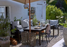 Dining table with chairs and bench under parasol on gravel floor