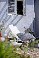 Deck chair with cushions under window on gravel floor