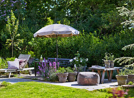 Terrace place with outdoor furniture, flowers and sunshade in summer garden
