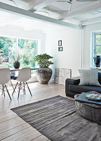 Open living room with wooden floorboards, dining table with classic chairs in the background
