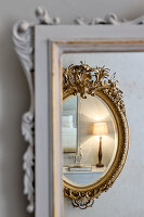 Reflection of a bedside lamp in the gold-framed mirror