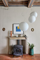 Disused fireplace with marble mantlepiece and cast-iron wood-burning stove; designer pendant lamp in foreground