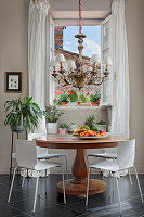 Ornate chandelier over antique round table with fruit plate, houseplants in background