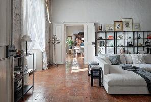 Open shelves and light sofa in high living room with terracotta tiles