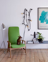 Green upholstered chair with dog between floor lamp and fairy lights