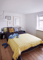 Double bed with bedspread in light bedroom with wooden floorboards