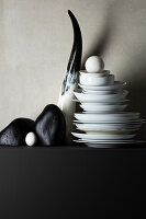 Black pebbles, horn and stacked plates on black ledge