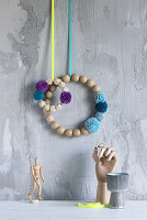 Wreaths of wooden beads and pompoms hung on wall with grey, structured, plaster surface