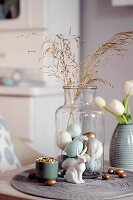 Colourful Easter eggs and grasses in a glass jar