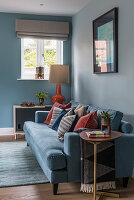 Rust-red scatter cushions on blue sofa against pale blue wall in living room