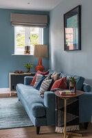 Blaues Sofa mit Kissen in Rostrot vor hellblauer Wand im Wohnzimmer