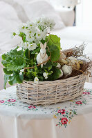 Basket with goblet primrose, horned violets and branches as an Easter basket with an Easter bunny and Easter eggs