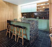 Kücheninsel mit schwarzem Terrazzo und grünen Fronten in offener Küche