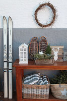 Wintry arrangement of skis and console table against outside wall