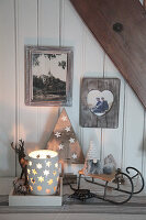 Wintry arrangement of candle lanterns, sledge and gnomes in shades of grey