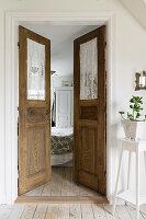 View through open, rustic double doors into the bedroom