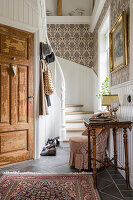 Antique console and armchair in hall with white wood panelling and medallion wallpaper