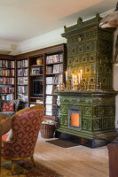 Green tiled stove and antique bookcase in the living room