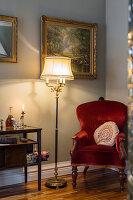 Bordeauxroter Polstersessel und Stehlampe in Zimmerecke mit Goldrahmenbild