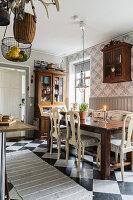 Holztisch mit Stühlen und antiker Vitrinenschrank in der Küche mit Schachbrettfliesen
