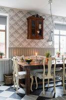 Holztisch mit Stühlen und antiker Wandschrank in der Küche mit grauer Holzverkleidung und Tapete