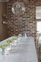 Windlichter auf langem Esstisch aus Holz, darüber Glas-Pendelleuchte