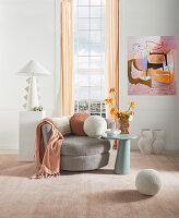 Feminines Wohnzimmer in Pastell mit grauem Sessel vorm Fenster