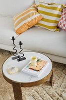 Runder Couchtisch vorm Sofa mit gemusterten Kissen