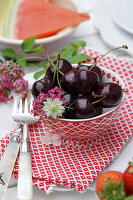 Bowl of 'Schwarze Knorpelkirsche' cherries with love-in-a-mist and pink yarrow flowers