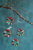 Tiny colourful Christmas wreaths made from felt squares hung from branch