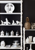 Porcelain figurines and Fornasetti decorations on a shelf in front of a black wall
