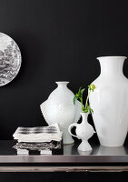 White vases in different shapes in front of black wall
