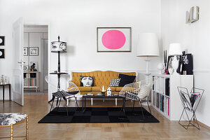 Picture with pink circle above the ochre sofa in the living room