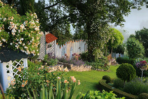 Hillside garden with rambler roses 'Ghislaine de Feligonde' and 'Lykkefund', English rose 'Crown Princess Margareta', catnip, lavender, covered shelf as a workplace