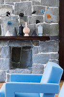 Light blue designer armchair in front of natural stone wall in living room
